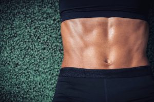midsection-of-muscular-woman-lying-on-carpet